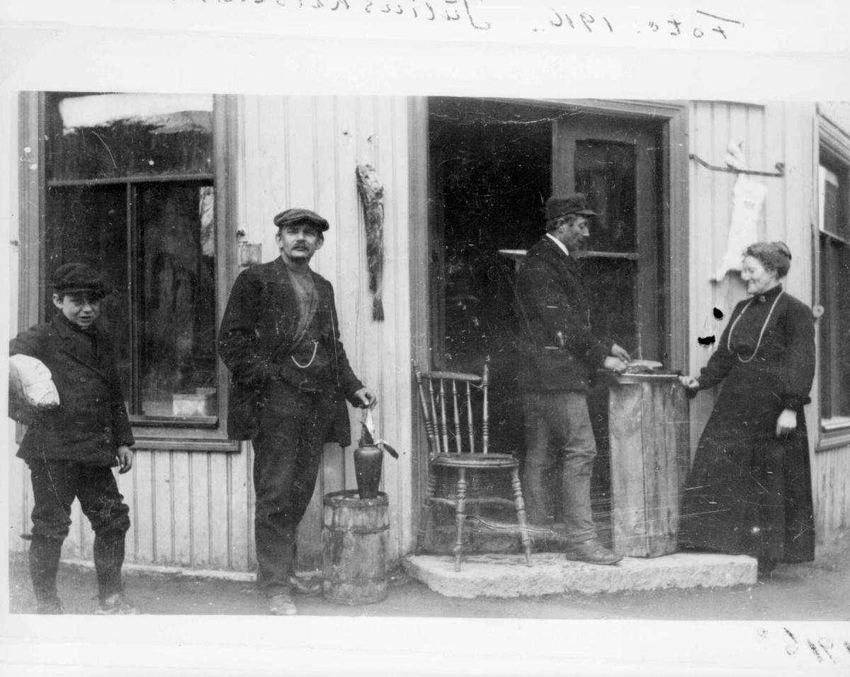 Repro: Åpen butikkdør med 4 personer utenfor. Speilbilde.