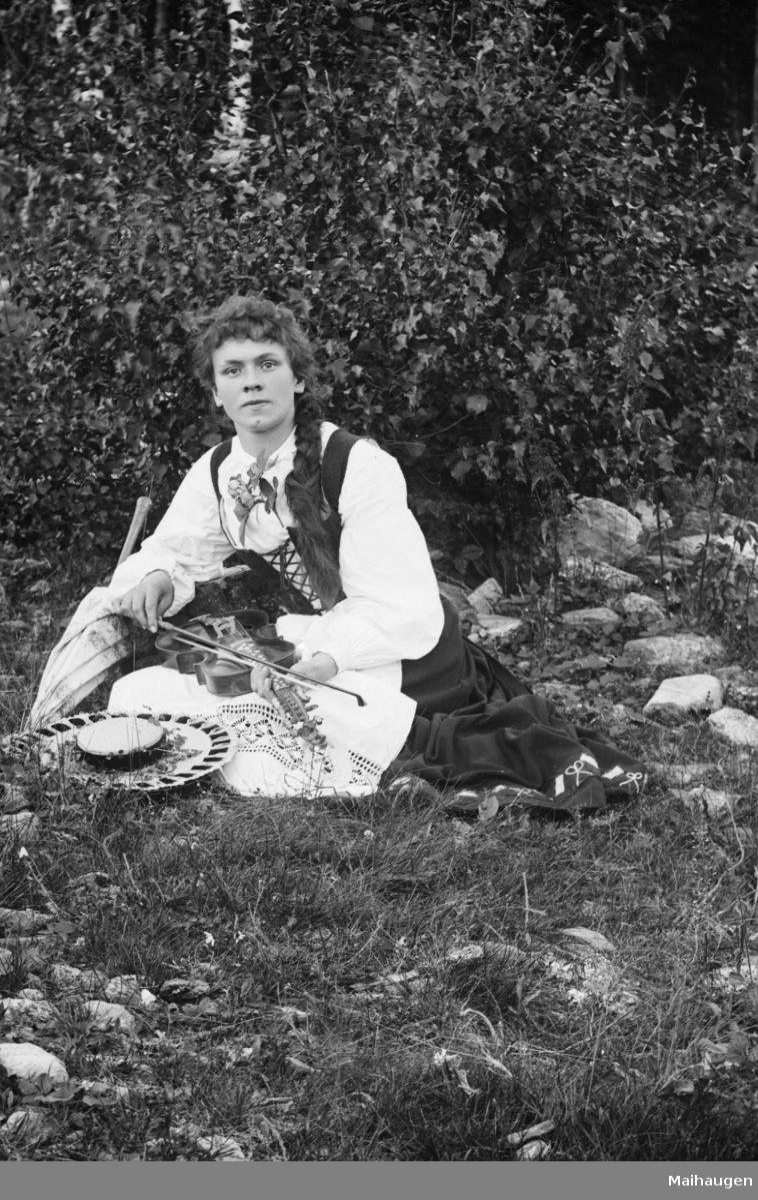 Portrett, ung kvinne i folkedrakt, sitter i gresset med fele, Anna Røine, lærerinne fra Nord-Fron, født i 1875