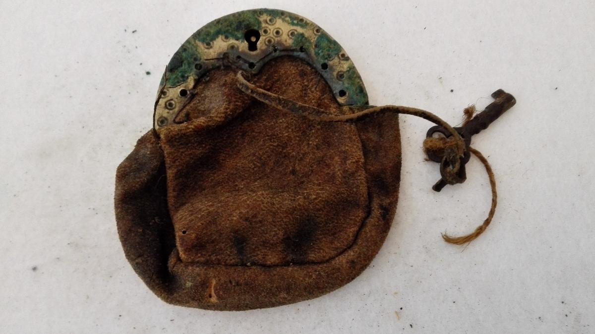 2 Skindpunger med messinglaas (12355 - 56)  12355 - Pung av semsket skind med 7,5 cm bredt messinglaas, forsirt med indstemplete prikker med ring omkring. Har laas og nökkel.  Gave fra Lars Bollingberg, Gaupne, Luster.
