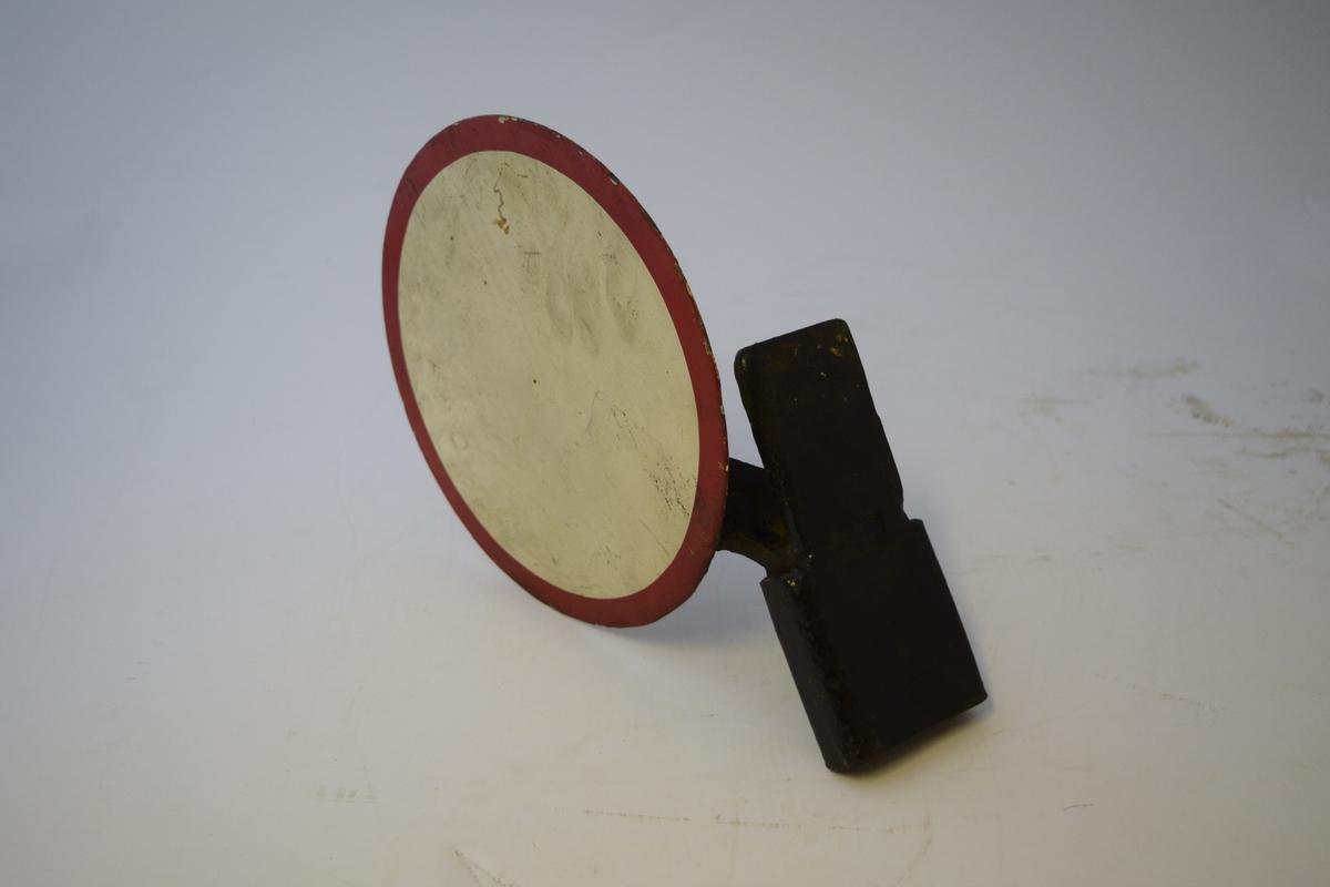 Rund metallplate malt hvitt med rød sirkel ytterst. Festet på holder i metall - malt sort. 2 stk., like, men speilvendte.