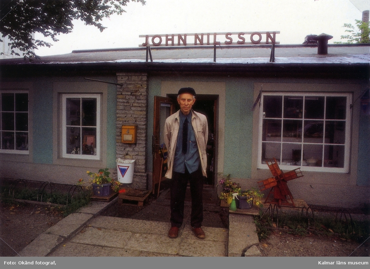 """John Nilsson """" John i muren """" framför sin butik i Degerhamn."""