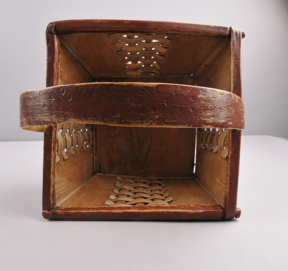 """Raudmåla korv av tre, med svidekor og fletta mønster i spon på alle fire sidene. Brenndekorert med mønster i kryss, samt ruter og sirkelmotiv. Korva er firkanta, og har ei hank.Hanka er nagla fasst til korva med trenaglar. Langs sidene og botten er det sett inn metallnaglar. Korva er fellt saman med """"treknappar"""" i aller fire hjørna."""