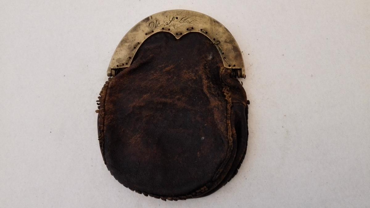 1 pung med messing laas.  Stor pung med glat pungelaas paa den ene side mærket Ole S. Æri og paa den anden side indridset OSE 1844. Laasets bredde 16,5 cm. Har to rum.  Disse tre gjenstande ( 7019-7020-7021 ), stammer fra Eri i Lærdal.  Kjöpt av landhandler Theodor Lindström, Lærdal.