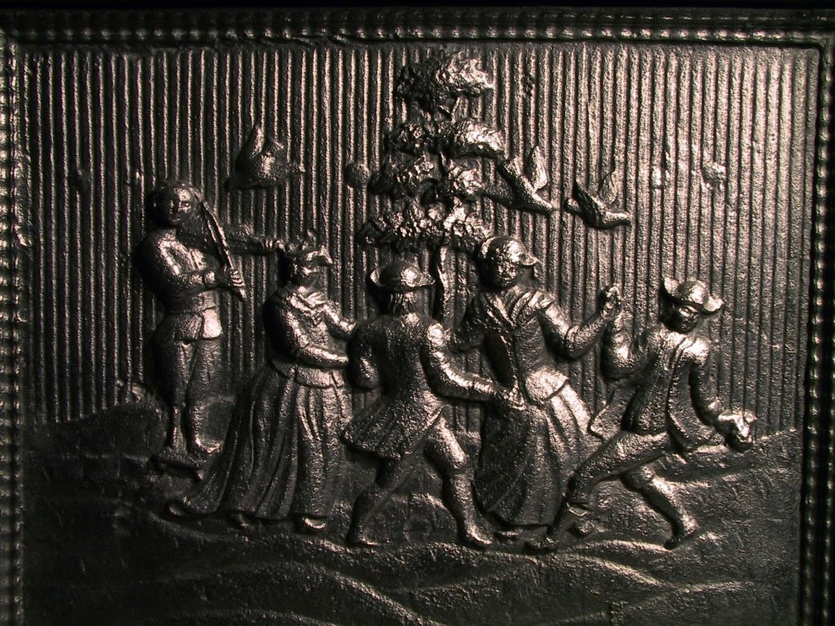 To bondepar i rokokkodrakter danser om et tre, t.v. felespiller med treben stående på lav krakk. Kortsiden øverst rokokko-ornament m. blomster, nederst Bolwigs O Wærck / 1781 i symmetrisk rokokkokartusj hvorover innskåret ONS ( = Ole Nielsen Weierholt). Ls II symmetrisk rokokkoornamentikk m. blomster. Ks. II blomstervase på usymmetrisk postament. Alle plater riflet bunn og springlist ramm.