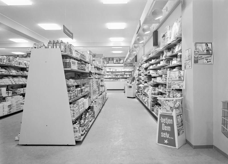 """Skiltet med """"Betjen Dem selv..."""" forteller at kundene måtte venne seg til nye måter å handle inn på i butikken.  Bildet stammer fra Asbjørn Olaussens kolonial i Strømmen 1965. Foto: Asbjørn Kåre Gundersen, MiA (Foto/Photo)"""