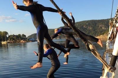 """Fire ungdommer i svømmedrakt hopper i vannet fra skonnerten """"Svanen""""."""