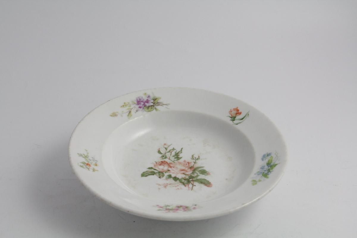 Runde dype tallerkener, tre stykker. Hvit bunn, polykrom blomstermotiv (naturalistisk) trykket på. Blomsterbukett på speil, fem mindre buketter på fane. Hver tallerken er forskjellig. Merket med produsentlogo under.