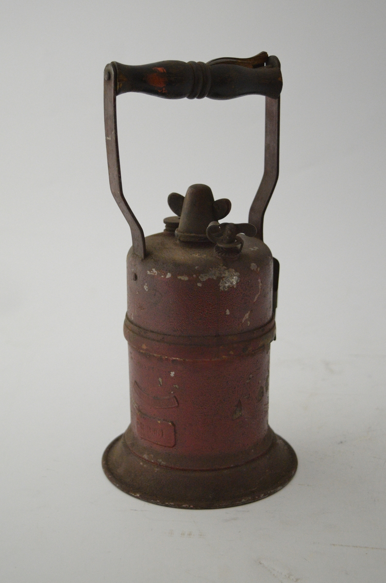 Arbeidslampe, karbidlampe. Håndholdt, sylindrisk from. Mangler reflektor. Rødmalt.