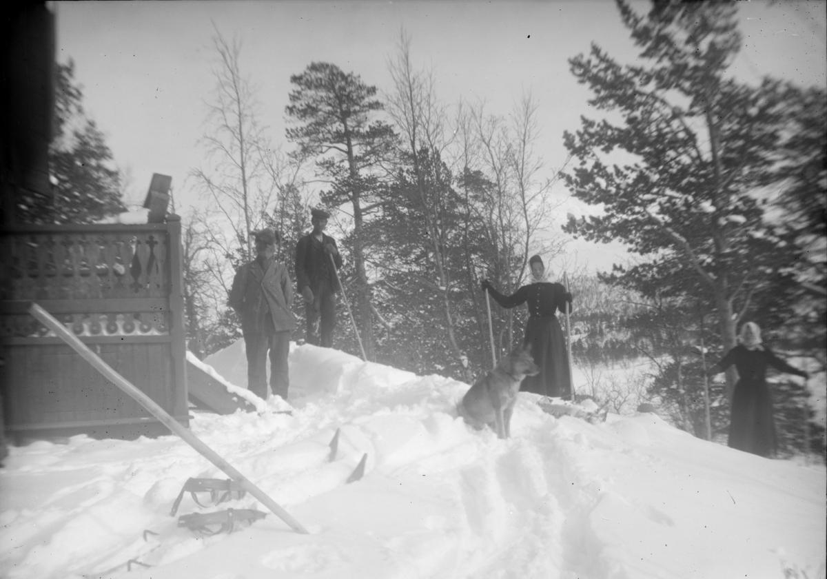 Eldre mann og hund ved hus sammen med en mann og to kvinner som står på ski