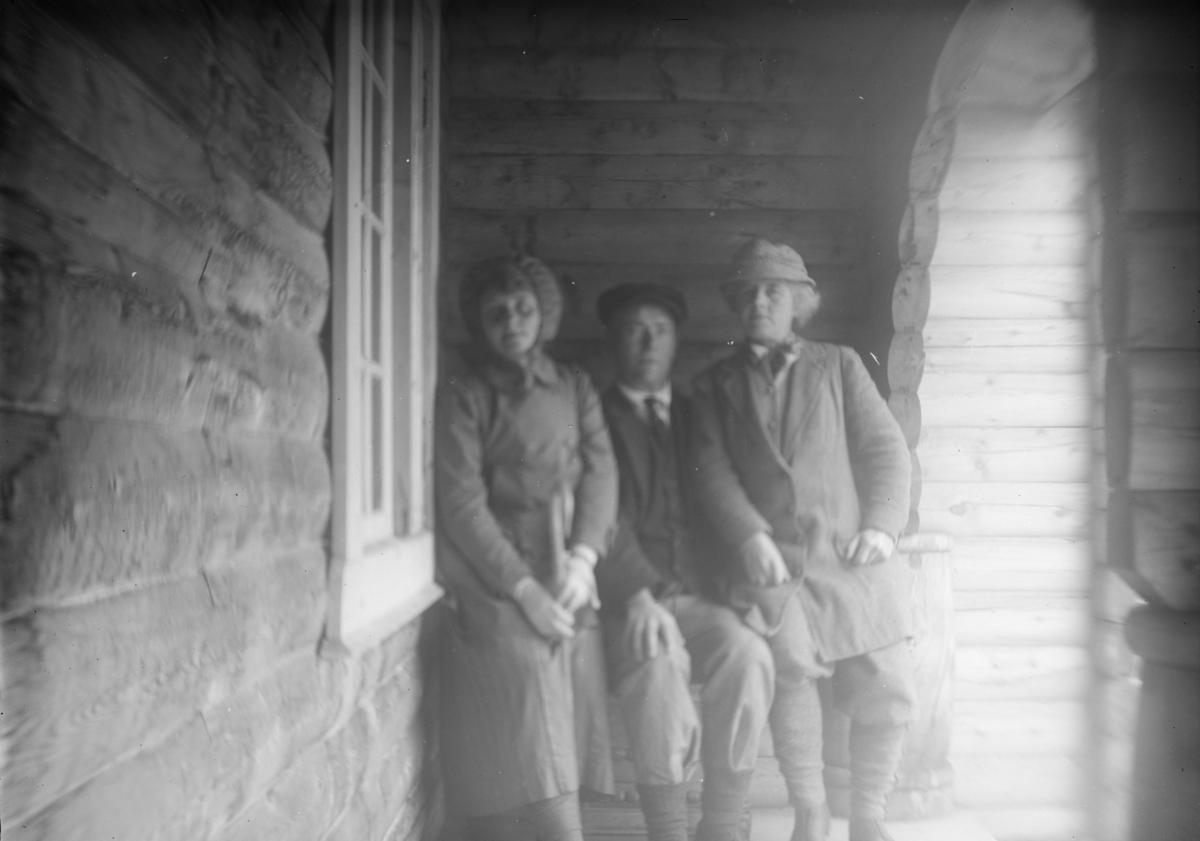 Sjodalen, En mann og to kvinner sitter under tak ved inngang til Bessheim