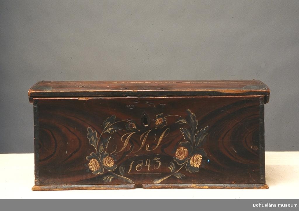"""Rektangulär med något välvt lock. Locket har tappad konstruktion. Ådringsmålad i mörkt brunrött och svart. Alla kanter och hörn är målade med blågrön färg. Framsidan har rosmålning i form av ett hjärta med initialerna """"IIS"""" samt årtalet """"1843"""". Baksidan är målad i (engelskt) rött. Lås i original med rombformad nyckelskylt. Inuti finns en läddika på vänster sida. Locket saknas.  Litt.; Anker, Peter, Kister og skrin, C. Huitfeldts förlag, Oslo, 1989.  Ur handskrivna katalogen 1957-1958: Skrin, trä """" IIS . 1843 """" L. 61,5, Br. 35, H. 27 cm;  rödmålad med ådring i svart, blå hörnen; framtill blommor i grönt vitt och rött. Nyckel saknas, maskäten.  Lappkatalog: 84"""