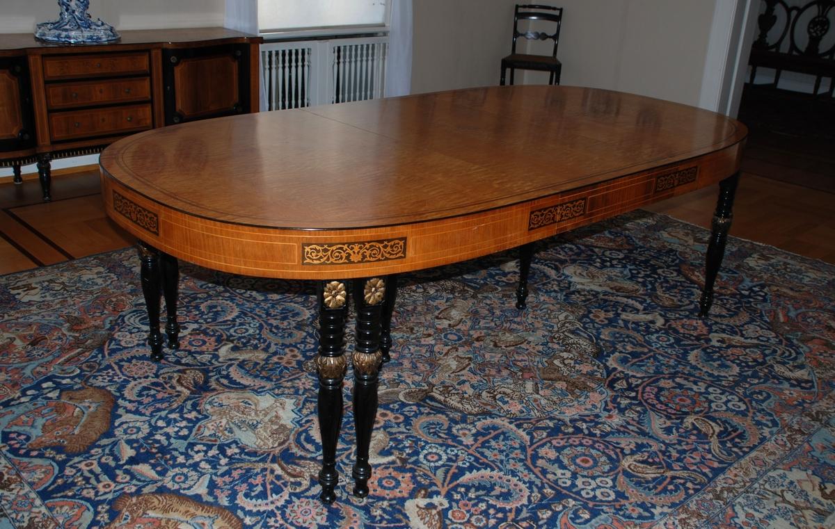 Uttrekkbart spisebord laget av snekkermesterfirma Knag i Bergen 1939. Lys finér, med intarsia på sidene. Benene er dreiede, sorte med gulldetaljer.