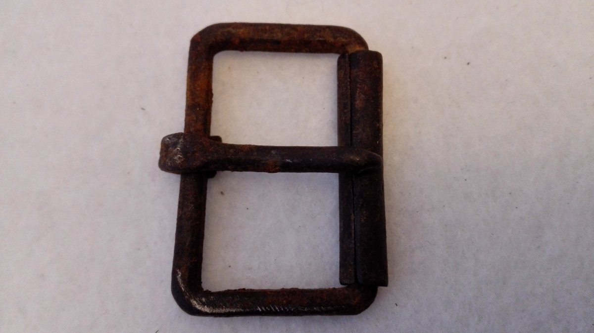 Form: Firkanta 1 spænde av jern.  Firkantet spænde av jern. 3,7 x 2,5 cm. Hjemmesmidd.  Gave fra Anders Jensen Ylvisaker, Norum.