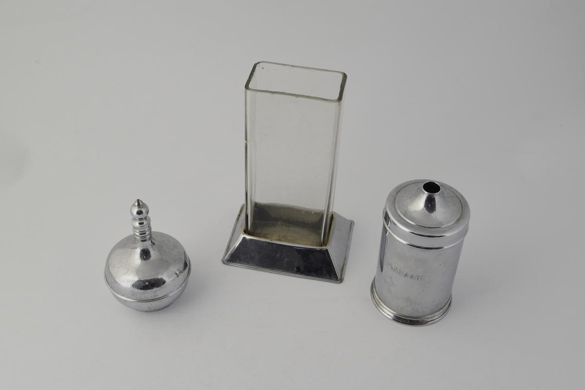 3 stk. beholdere. a) høy rektangulær beholder av glass med løs metallfot. b) sylinderformet med lokk med hull i, inneholder bomullsdotter. c) Flakong, sirkulær med smal lang hals.