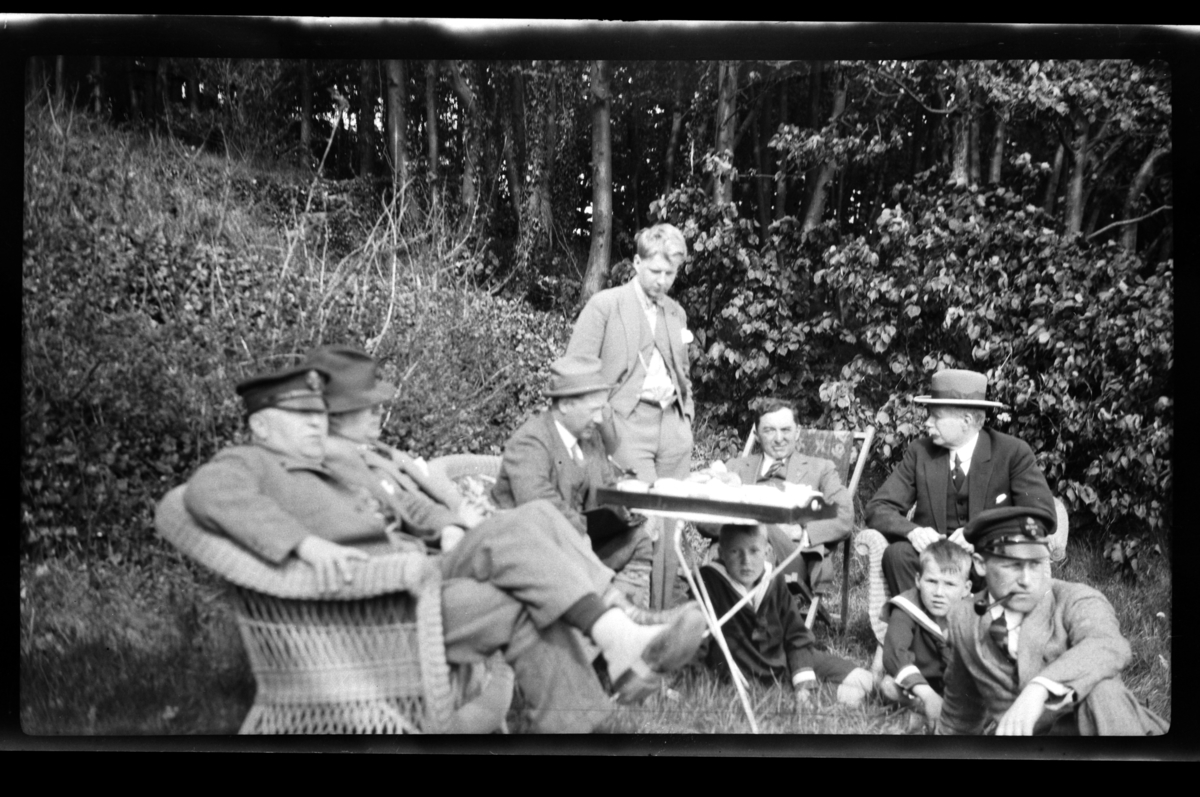 Gruppe av unge og gamle menn samlet rundt et bord i hage. Fra venstre Halfdan, Trygve, Finn og Bjarne Sundt, Johan Buratti, Christen og Bjørn Reymert og Peter Sundt. Ukjent gutt under bordet. Fotografert 1928.