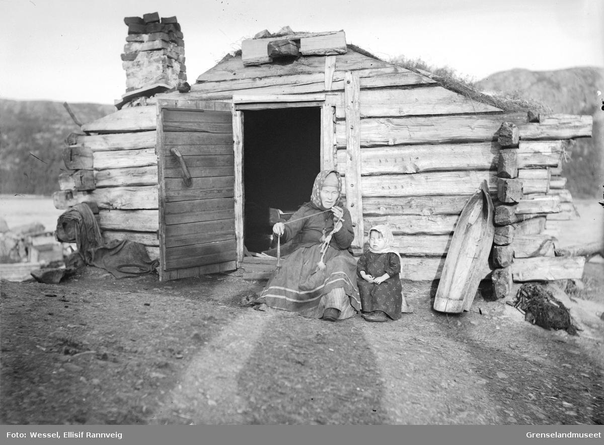 Skoltesamekvinne og barn utenfor sitt hjem i Boris Gleb. Kvinnen spinner på håndtein.