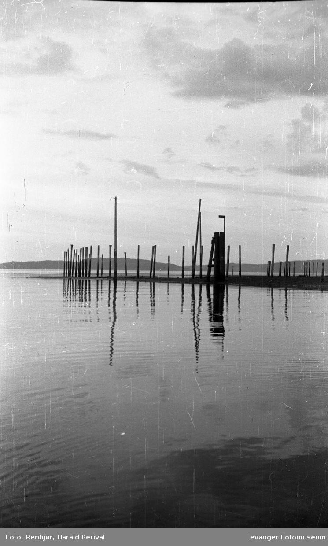 Fjordlandskap, med pæler i sjøen.