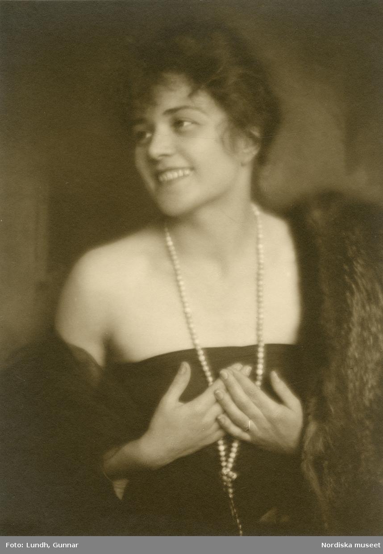 Porträtt av leende kvinna i mörk klänning, halsband och päls. Varuhuset Wertheims porträttateljé, Berlin.