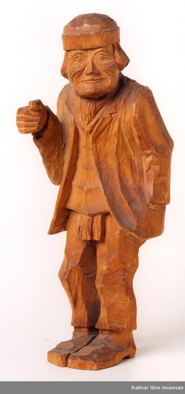KLM 39255:8. Skulptur, av trä. Gubbe i kavaj och halsduk under tröja. På huvudet mössa utan skärm. Defekt, föremål i höger hand saknas. Signerad B. Ljunggren, Markaryd, 1919.
