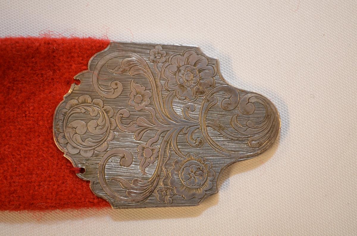 """Belte i raudt klede påsett ti stølar av sølv i filigransarbeid. Kvar plate (støl) er belagde med filigransknuppar, sølvkuler, to blåe steinar og ein støypt gravert knapp som er felt inn i plata. Sju runde skåler, fire opp og tre nede. Stølane er festa til belte med ei skinnreim på baksida.  I eine enden på beltet ei rektangulær spenne i filigransarbeid. I den andre, spjotenden, ei gravert sølvplate. På baksida av denne står initialane MJDR. Sannsynlegvis Marit Jørgensdatter Rengestad (1799-1882), eldste dotter til Jørgen). Belte vart """"reparert"""" i 1977 (sjå arkivkort VF 1235 b)."""