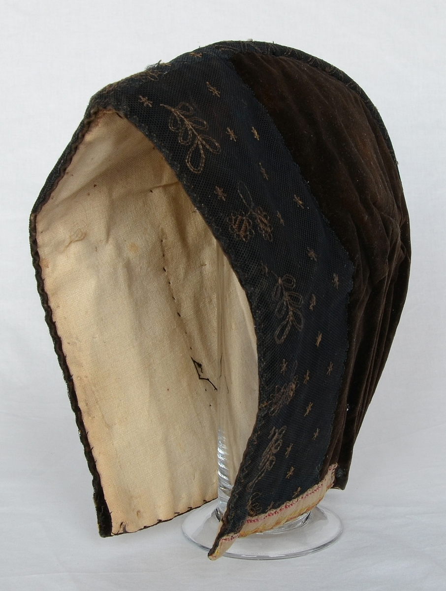 Kvinnomössa, kyrkmössa, brunsvart sammet med broderad svart tyll framtill. Linnefoder.
