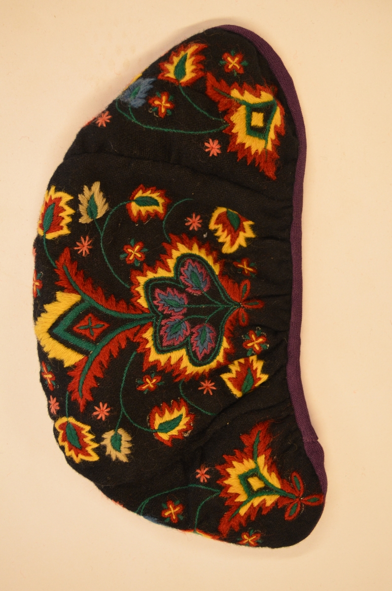 Lue , bunadlue i svart kledestoff med blomstermønster i ulike fargar. Fóra i svart bommull. Lilla band rundt kanten.
