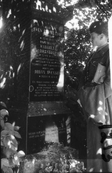 Ljunggren, sergeant, A 6 vid en gravsten.