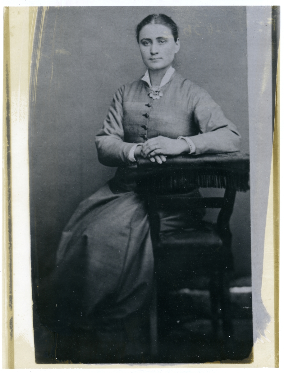 Portrett av ei ung kvinne. Kvinna har på seg ein lys kjole med ei sølje i halsen. Kvinna sit på ein stol og ho kvilar armane sine på armlenet til stolen. Armlenet har frynsar.