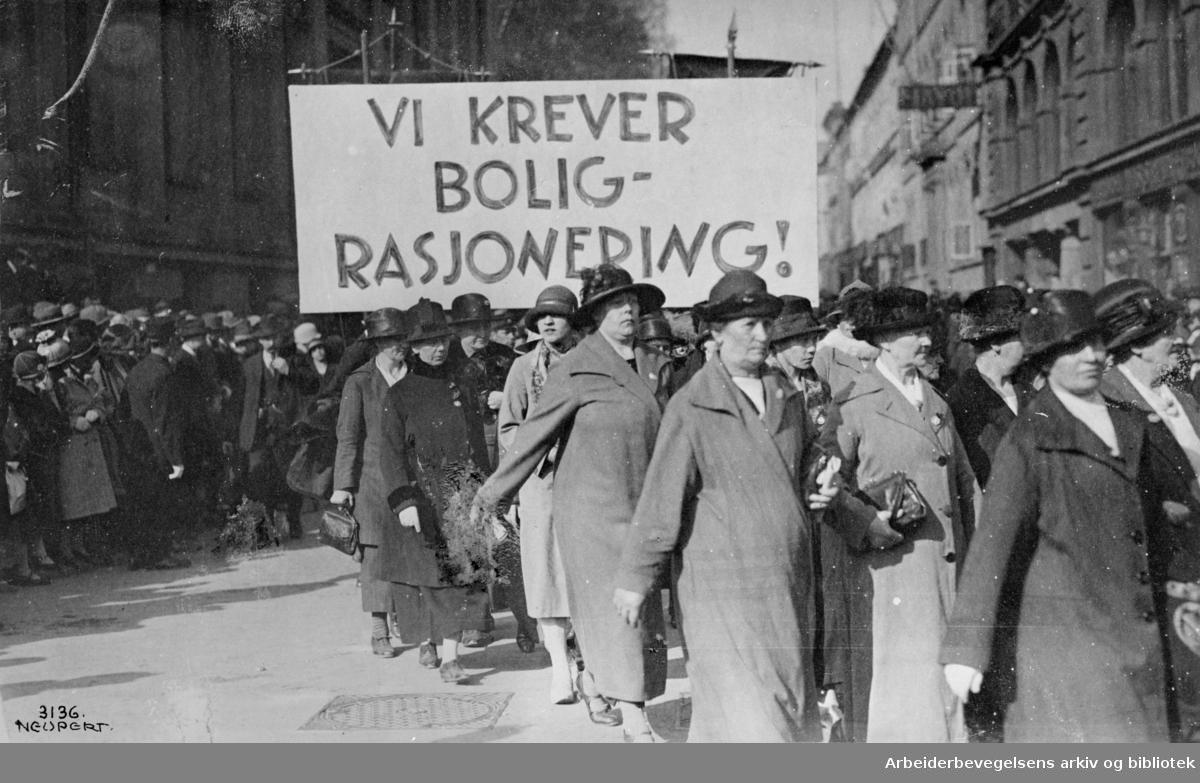 1. mai 1925, Arbeiderpartiets kvinneforeninger i Oslo. Demonstrasjonstoget svinger inn på Karl Johans gate fra Universitetsgata. Parole: Vi krever boligrasjonering!..