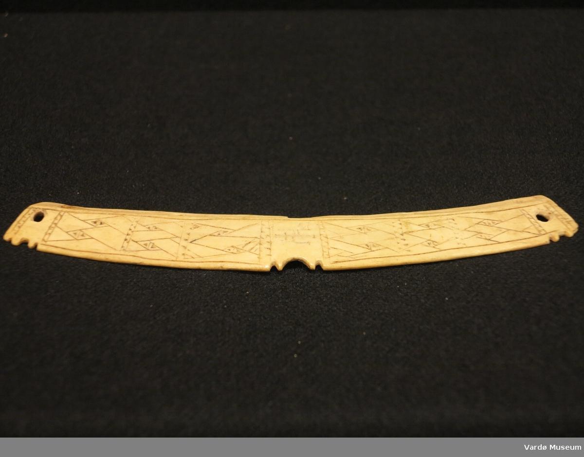 Ornamentert veskelås med utskjæringer og fire hull gjennom gjenstand.