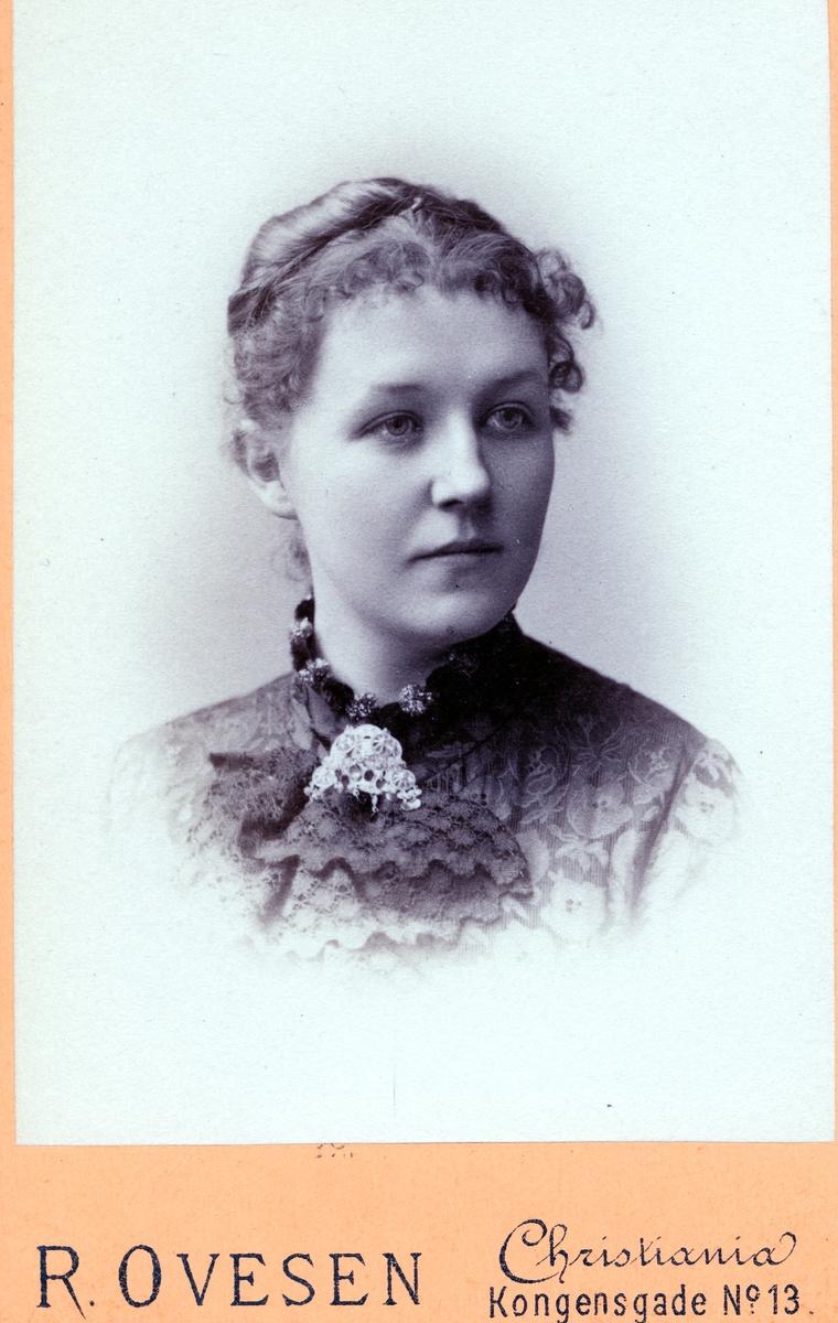 Portrett av kvinne med blondekjole på. I halsen har ho ei sølje.