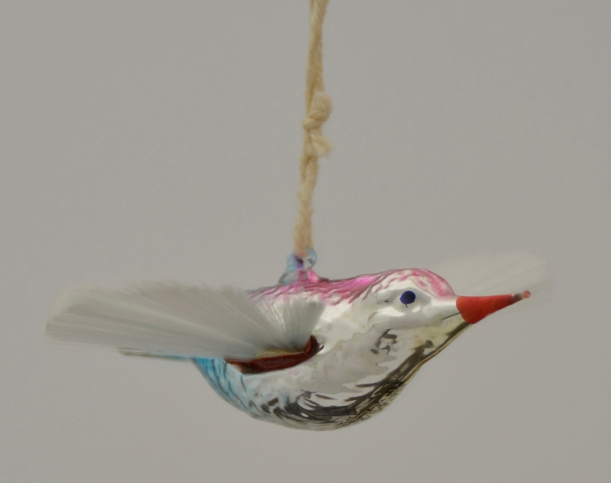 Juletrepynt. Glasfugl med vinger som ei vifte av silkeaktig, stiv tråd. Glaset er sølvfarga i botn med lilla og blått på kroppen og raudt nebb. Tråd gjennom oppheng på ryggen.