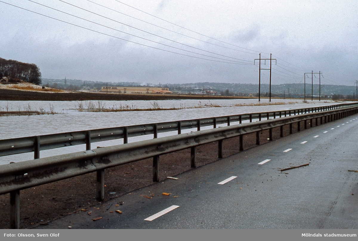 Fässbergsdalen i Mölndal den 23 mars 1986. Stora ån har svämmat över. Söderledens vägbanor närmast ån är översvämmade. FD 2:10.