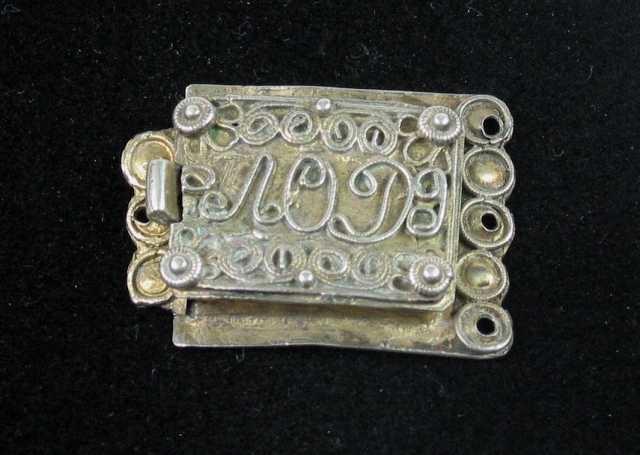 Låsespenne av forgylt sølv med samme låsemekanisme som SS-14376. Platen med låshuset er glatt men ender ytterst i små drevne tunger som hver er omgitt av en tvinnetrådsring. Det er festehull i tre av tungene. Låshuset er på oversida kantet med tvinnetråd med perlekruser i hjørnene. Hele flaten er fylt med filigransarbeid og monogrammet AOD. Den andre delen av spenna er ganske kort og smal med tre drevne tunger omgitt av tvinnetråd. Ett festehull. Til dette stykket er det loddet en fjær som beskrevet under forrige nummer.
