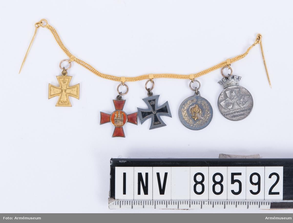 """Fem miniatyrmedaljer på guldkedja med nålar, att bäras till frack. 1. Militärförtjänstkorset från Mecklenburg-Schwerin, i guld med storhertig Friedrich Franz II:s initialer och 1914, i rött, gult och ljusblått band. 2. Hansakorset från staden Hamburg, med stadens vapen i centrum på det rödemaljerade korset, i rött och vitt band. 3. Järnkorset av II klassen, 1914 i svart-vitt band. 4. Okänd medalj med fransk lilja. 5. Medalj för Stockholms befälsutbildningsförbund, med texten """"fäderneslandets försvar""""."""