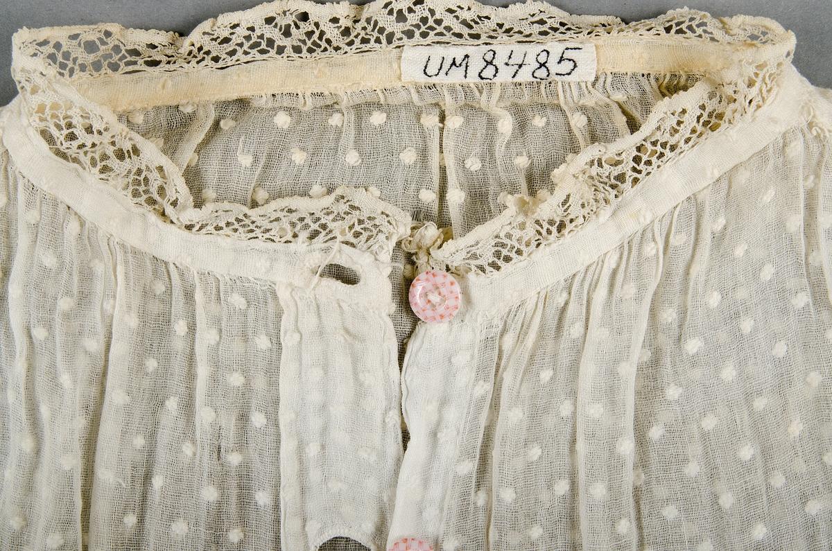 Blus, s.k. garibaldiskjorta, av vit bomullsvoile med små broderade prickar. Fram- och bakstyckena helt raka. En 2 cm bred bit är infälld på axlarna. Ärmarna är rynkade med smal linning med spets i kanten. I halsen en smal linning med spets. Knäppning fram med sex knappar. Knäppning på ärmlinningarna. Knapparna är små vita porslinsknappar med rosa rutor.
