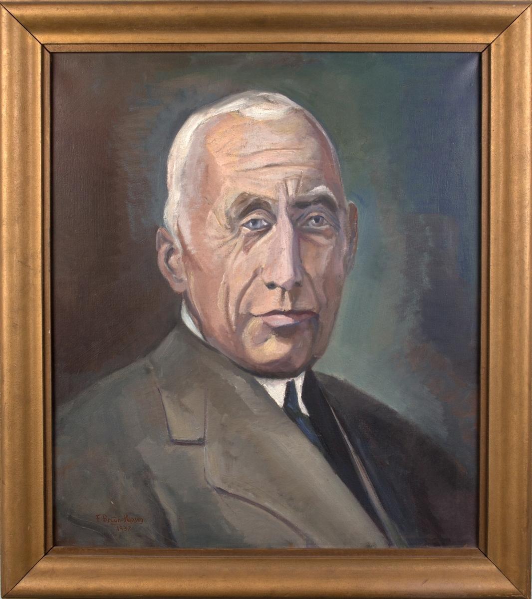 Brystportrett av Roald Amundsen. Han er hvit i håret, og er iført lys dressjakke, hvit skjorte og blått slips.