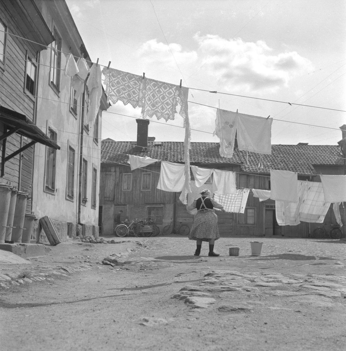 Bakgård vid Snickaregatan 11.   Bilden är tagen mot söder mitt i kvarteret Blåklockan mellan Ågatan och Storgatan. På gården hänger en kvinna tvätt på uppspända linor. I bakgrunden, vid den ena byggnadens fasad, syns en man bredvid ett antal cyklar; i uthusräckan inrymdes Wallins cykelverkstad, med gatuadress Storgatan 9. Verkstaden innehades av Sixten Wallin, far till musikern Bengt Arne Wallin.