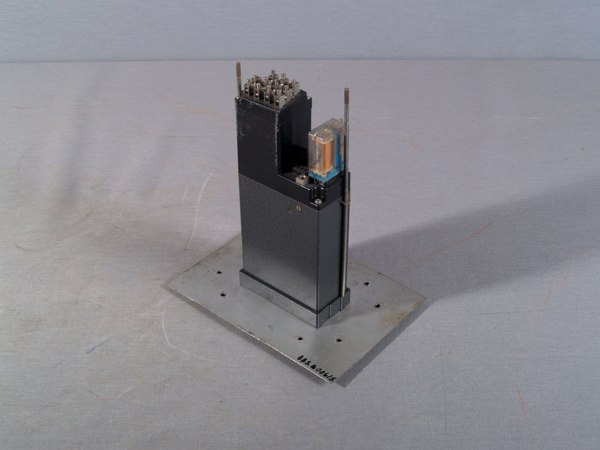 Elektrisk instrument for høydemåling, vann, med 9 koblingspunkter og relékontakt. Instrumentet mend for veggmontering, og har visningsvindu i med meterskala i frontplaten.