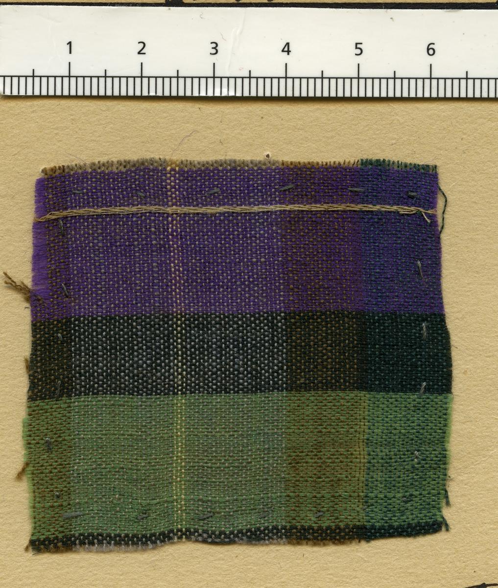 Anmärkningar: Vävprov av halvylle i tuskaft, rutigt. Bomullsvarpen är randad i beige, vitt, rostbrunt och blått. Inslaget av ull är randat i grönt, svart, lila och beige.