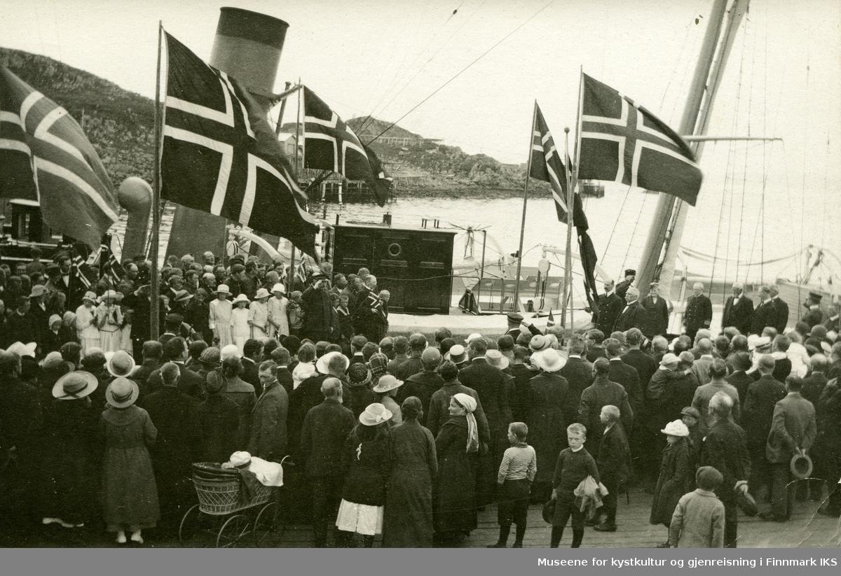 """Postkort. Kongebesøk i Honningsvåg. Kong Haakon VII går i land fra """"Heimdal"""" på dampskipskaia. Feststemte folk med flagg møter kongen. 28.06.1922."""