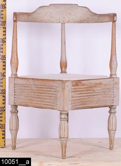 """Anmärkningar: Puderstol, sengustaviansk, omkring 1790.  Rundat överstycke med kontursågad mitt. Tre balusterformade ryggstolpar. Kvadratisk form på sittdelen. Löstagbar stoppad sits. Förvaringsutrymme under sitsen (bild 10051__c). De fyra plankformade sargarna som förbinder benen är samtliga räfflade. I varje hörn finns ett ben. Benen har överkragningar med skurna lansettblad, därefter lansettformade skurna bladhölster. Därunder är benen nedåt avsmalnande och kannelerade, fotavslutningarna är svarvade (bild 10051__b). H:840 Br:630 Dj:630  Hela stolen är av ljust lövträ utom bottenstycket som är av furu. Stolen är gråmålad och är naturligt sliten.  Tillstånd: Sitsen är senare.  Historik: Enligt liggaren är stolen """"Inköpt av en jude"""", Sala, på 1930-talet. Stolen har deltagit i utställningen """" Samlat 1700-tal """"."""