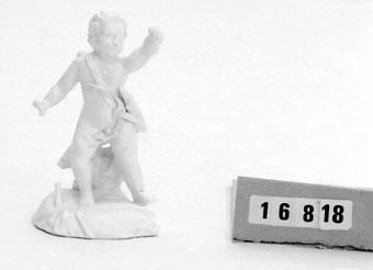 """Anmärkningar: Figurin vit, av mjukt porslin. Amor med koger. Skadad. Marieberg, Berthevins eller Steens period. (Har en gång tillhört den Westerdahlska samlingen som skingrades på 1920-talet). """"Märta och Karl Adolphsons samling."""" Donation 1971 av advokat och fru Karl Adolphson Randersg. 1. Helsingborg."""
