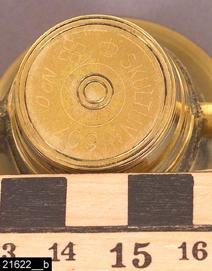 """Anmärkningar: Mortel med stöt, omkring 1983.  Rund profilerad mortel med genombrutna öron på sidorna och en profilerad stöt (som har invnr. 21623). Parallella dekorationslinjer löper runt morteln och vid öronen rombformad dekor. På mittpartiet, där årtalet 1607 samt krona är ingjutet i relief, är gjutytan lämnad rå. Undertill är morteln märkt """"SKULTUNA 1607 No 0"""" (bild 21622__b). Tidsangivelsen grundar sig på tidpunkten för förvärvet av föremålet till museet. Enligt en broschyr, utgiven av museet 2007 och benämnd """"Skultunastämplar 1800-2000"""", började den typ av stämpel som finns på föremålet användas 1922. Den användes fortfarande år 2007. H:45 Br:55 D:50 Stötens längd:80  Tillstånd: Nyskick.  Historik: Inköpt tillsammans med invnr. 21623 från Skultuna Messingsbruk i samband med länsmuseets samtidsdokumentation vid bruket, 1983, för 96,40 kronor + moms."""