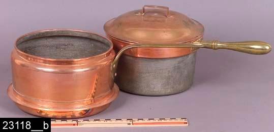 """Anmärkningar: Grötkokare, 1910/1930-tal.  Grötkokare med lock, insats och fals för placering på järnspis med upplyftbara ringar (bild 23118__a-b). Den yttre kastrullen är cylindrisk och är något inkragad vid mynningen och har platt handtag av mässing fästad vid kastrullen med triangulärt fäste. Insatsen är cylindrisk och är utkragad vid mynningen (så att den hänger ovanpå den yttre kastrullens kant) samt har runt handtag av mässing. Locket är välvt och försett med hsndtsgBåda kastrullerna är tillverkade av koppar och invändigt är de förtennta. På tre ställen finns stämplar i form av en krona samt texten """"SKULTUNA 1607"""". På två av ställena anges också volymen """"2 1/2 L."""" (bild 23118__c). Grötkokokaren finns avbildad och nämnd i kataloger från Skultuna från 1910-1930-talen. I en katalog från 1933 står följande: """"Grötkokare n:r 334, med lock, blankpolerade, invändigt förtenta, med skaft av mässing"""". Modellen tillverkades i tre storlekar; 2, 2 1/2 samt 3 liter. Mellanmodellen kostade 13,70 kronor (bild 23118__d). Enligt en broschyr, utgiven av museet 2007 och benämnd """"Skultunastämplar 1800-2000"""", började den typ av stämpel som finns på föremålet användas 1922. Den användes fortfarande år 2007.  Tillstånd: Nyskick.  Historik: Gåva från Dagmar Svensson, Bärkevägen 15, Söderbärke, 1987."""