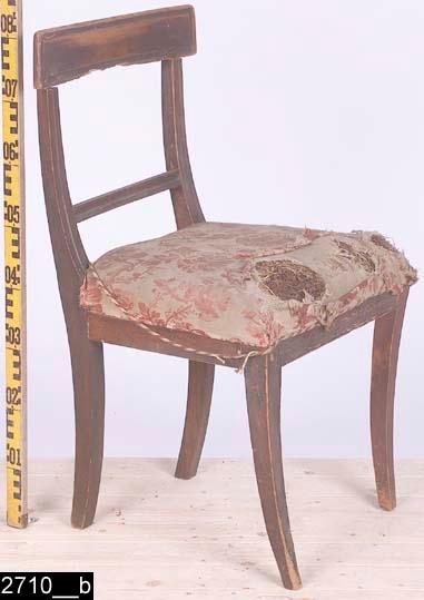 Anmärkningar: Stol, Karl Johan, 1800-talets första hälft.  Svagt konvext överstycke. S-svängda bakstolpar (bild 2710__b). Genombruten rygg med en ryggslå. Överstycket och ryggslån är profilerade. Stoppad sits med blommigt tyg (bild 2710__c). Fyra utåtsvängda ben (bild 2710__b). H:810 Br:460 Dj:470  Hela stolen är av ljust lövträ utom två sargar och bakstolparna som är av furu. Hela stolen är mörkröd, överstycket bär spår av naturligt slitage.  Enligt kortkatalogen saknas fyra stolar (ursprungligen bestod invnr. 2710 av 6 poster). De saknade stolarna finns ej i 2003 års inventeringsförteckning över Vallby. En post har splittrats av projektet Sesam och har fått invnr. 25693.  Tillstånd: Överstycket och framsargen är maskstungna. Överstyckets undersida är skadat. Stoppningen och tyget är skadade. Höger framben är senare.  Historik: Gåva av Holmberg, Västerås 1923.