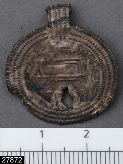 Anmärkningar: Badelunda sn, Tuna undersökt 1952-1953 Hänge, från båtgrav daterad till yngre järnålder, 850 e.Kr. (Vikingatid)  Hänge av silver från grav 75. 1 st av tunt bleck pressat över ett arabiskt mynt från Wäsit 125 e.H. (742/43 e Kr.). Kant av tre pärlade ränder, upphängningsöglorna urklippta ur samma bleck som hängena och ornerade med pärlade ränder. Hängena var åtskiljda av små vita eller blå glaspärlor. (Myntbestämningar av Ulla Linder Welin) Diam 25 x 22 mm Tjl 0,3 mm Utställd Forntid 2014  Hänge nr 2 av 2? st som utgör fynd 20.  De två hängena funna med pärlor på sidorna, i ordning: 2 blå på var sida om 3 vita. I graven (75) fanns fjorton hängen av tunt silverbleck, förseddan med bandformiga öglor. Tolv av hängena är identiskt lika med arabisk text inom en rundel omgiven av tre pärlränder längs kanten.  Mycket skör, har nästan gått av vid kanten intill upphängningsöglan (2008-08/SG-Access)  Litteratur Nylén, E. & Schönbäck, B. 1994. Tuna i Badelunda. Guld kvinnor båtar I. Västerås kulturnämnds skriftserie 27. Västerås. s 44ff. Nylén, E. & Schönbäck, B. 1994. Tuna i Badelunda. Guld kvinnor båtar II. Västerås kulturnämnds skriftserie 30. Västerås. s 112 ff, 150ff, 200.  Fotograferad teckning negnr A-7422