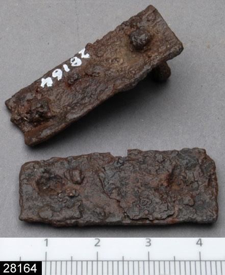 Anmärkningar: Badelunda sn, Tuna undersökt 1952-1953 Beslag, från brandgrav daterad till yngre järnålder, 900-talet e.Kr. (Vikingatid).  Remändesbeslag av järn från grav 33, 2 st. Rektangulära, i ena beslaget en nit. Beslagen har troligen tillhört en betselutrustning. L 40 mm Br 17,5 mm. Nitens L 15 mm  Litteratur Nylén, E. & Schönbäck, B. 1994. Tuna i Badelunda. Guld kvinnor båtar II. Västerås kulturnämnds skriftserie 30. Västerås. s 44 ff, 84, 199.  Fotograferad teckning neg nr A-7404