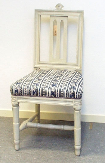 """Anmärkningar: Gustaviansk stol, troligen stockholmsarbete. Gråmålad. Rakt kälat ryggkrön med uppskjutande skulpterad dekor i form av en humlekvist. Ryggståndarna , liksom tvärslå i nedre delen är kälade.  Ryggbricka med genombruten dekor i två skåror. Stoppad sits. Stolssargen på tre sidor kälad. Kraftigt profilerat fotkryss. Rosettanfang på frambenen, som är kannelerade med s.k. strumpa vid fotkrysset. Det bakre stolsbensparet är enbart kannelerat med en skåra på framsida. Frambenens fötter har en ansvällning, där de övergår i strumpan. Hör till samma uppsättning som invnr. 28406-28415. Omtapetserade. Två sprickor i ryggbrickans nederdel, varav en genomgående. """" 436F"""" skrivet under framsargen.  Har använts och används ännu på Sätra brunn."""