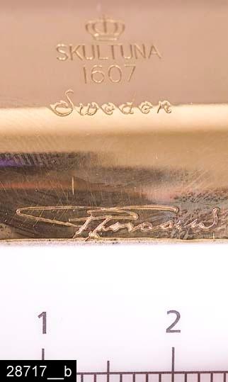 """Anmärkningar: Ljusstake, """"Solskiva"""", 1970/80-tal.  Cylinderformad ljusstake med snedställda kanter och plats för ett smalt ljus i mitten. Undertill är ljusstaken märkt """"SKULTUNA 1607 Sweden P. Forssell"""" (bild 28717__b). Pierre Forssell var formgivare på Skultuna 1955-1986. Till ljusstaken hör en originalkartong (bild 28717__c). I kartongen ligger en broschyr om ljusstaken (bild 28717__d). Tidsangivelsen grundar sig på att kartongen är märkt """"Gränges-Essem Skultunaverken"""". Gränges-Essem ägde Skultunaverken 1973-1983 (Gränges-Essem ägde Skultuna tidigare, men det var först 1973 som namnet Skultunaverken antogs). Enligt en broschyr, utgiven av museet 2007 och benämnd """"Skultunastämplar 1800-2000"""", började den typ av stämpel som finns på föremålet användas 1922. Den användes fortfarande år 2007. H:40 Br:60 Dj:40  Tillstånd: Nyskick.  Historik: Gåva från SAPA AB, Division Service, 2002. Föremålet stod i ett skyddsrum på bruksområdet i Skultuna."""